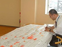 膨大な事務作業の流れを表にして点検中。こうして無駄な作業をあぶりだす