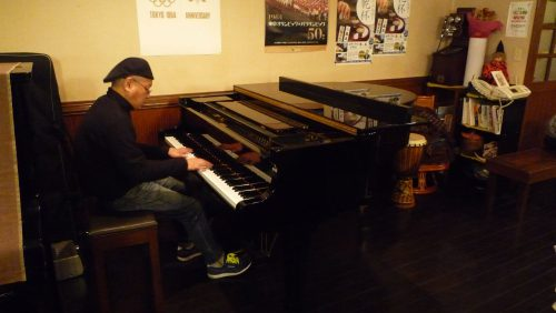 24年間続いている、ピアノの生演奏。毎週、木曜と金曜の夜は弾き語りを楽しみながら、食事とお酒を楽しむことができる(演奏者:髙橋一郎)